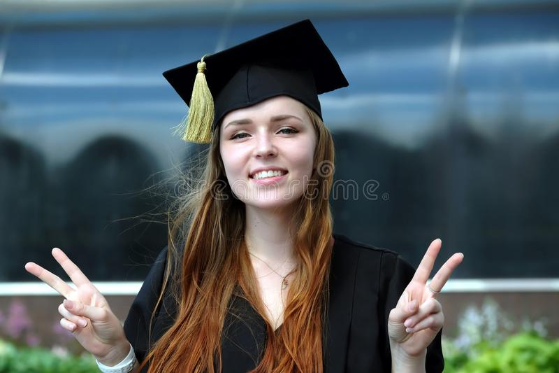 Graduiertes junges Mädchen mit dem roten Haar, das im Umhang gekleidet wird und quadratische akademische Kappe lächeln im Univers stockfotos