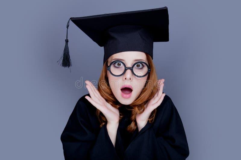 Graduiertes Mädchen in der quadratischen akademischen Kappe und im Umhang lizenzfreie stockfotos