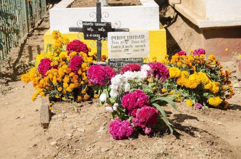 Graf met bloemen wordt verfraaid die stock fotografie