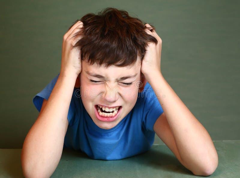 Graffio del ragazzo la sua testa isolata sul blu fotografia stock