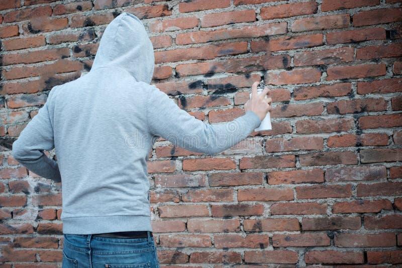 Graffiti à capuchon d'écriture de tagger sur les murs urbains photographie stock libre de droits