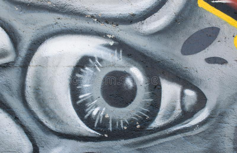 Graffiti art in the city street showing the painted eye on the concrete gray wall as background. stock photography