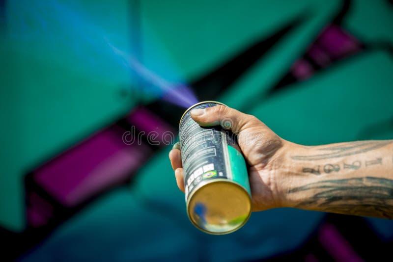Graffiti art spray painting action. Man drawing graffiti panel with blue ink brush spray tube stock image