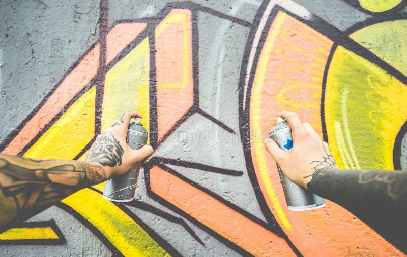 Graffiti artiest schilderen met kleurspray op de muur - Tattoed writer op het werk in de voorstad - Urban, straatkunst, royalty-vrije stock afbeelding