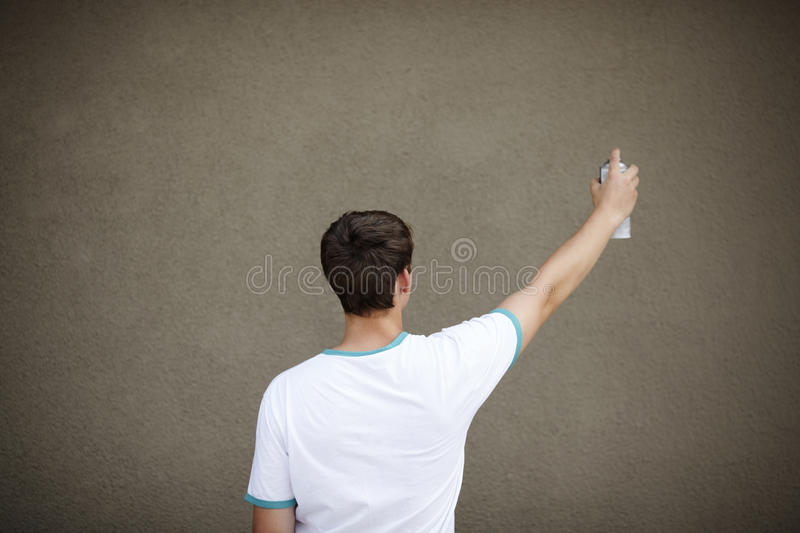 Graffiti Artist with Copyspace. Young teen with paint spray and empty areas for your text, selective focus on head stock image