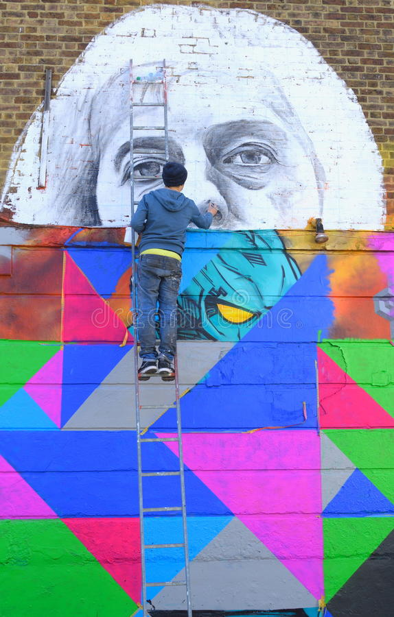 GRAFFITI ARTIST. On a ladder painting wall in Camden Town, London