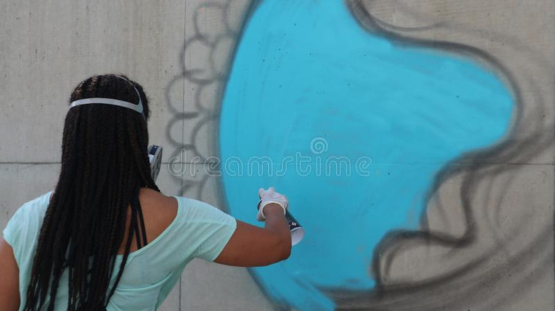 Graffiti artist spray paints a piece on a wall. French graffiti artist Kaldea spray paints a wall on December 1, 2018 at Alliance Francaise in Bangkok, Thailand stock photography