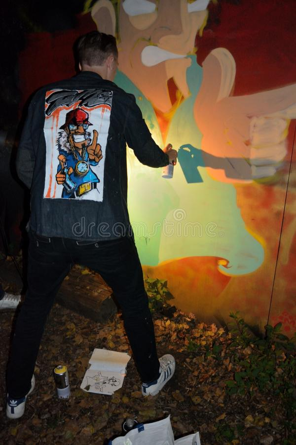 Graffiti artist at work. GENT, BELGIUM,21 SEPTEMBER 2014:Graffiti artist named:Time 247, demonstrating his talent at a party in the tuin van Heden a famous bar royalty free stock image