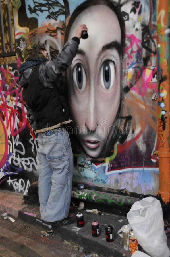 A graffiti artist at work. Streeti artist putting the finishing touches to a graffiti on a wall of the Undercroft, London,Uk stock image