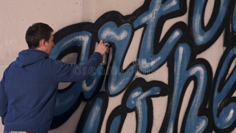 Graffiti artysty obraz z aerosolową kiścią na ścianie zdjęcia stock
