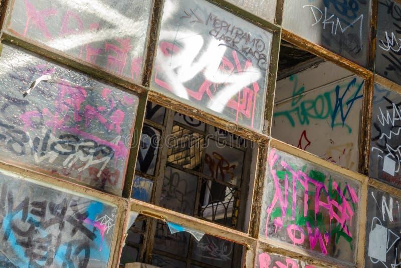 Graffiti auf zerbrochenen Fensterscheiben stockfoto