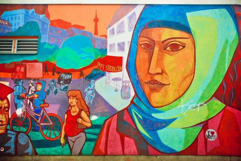 Graffiti avec le visage de la femme dans le hijab vivant dans le secteur des immigrés image libre de droits