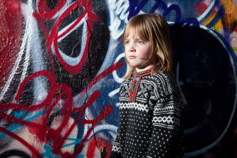 Graffiti child cool street art. Child in front of graffiti wall in urban area. Cool young boy by street art in deprived town area royalty free stock images