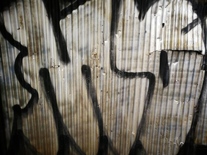 Graffiti on corrugated metal. A corrugated metal wall with graffiti painted on it royalty free stock photo