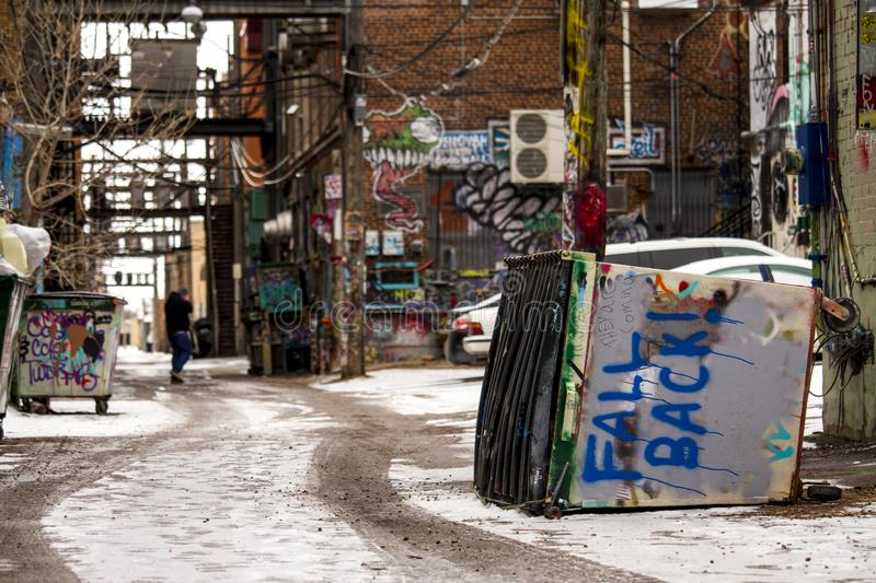 Graffiti covered Art alley, Dumpster tipped. Dumpster tipped warning BACK OFF spray painted in blue as man walks by in the back ground. Art Ally Rapid City SD stock photo