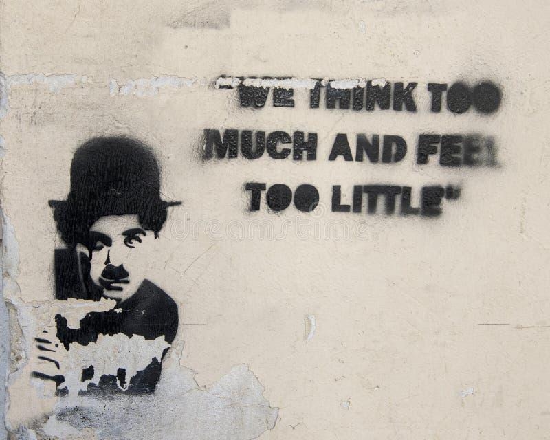 """Graffiti déchiré en lambeaux avec l'image Charlie Chaplin et la partie d'une de ses citations célèbres, """"nous pensons trop et nou image libre de droits"""