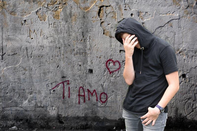 Graffiti del Ti AMO e ragazzo infelice con la maglia con cappuccio nera immagini stock