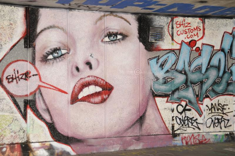 Graffiti depicting the face of a young woman with bright red lips. Colourful graffiti depicting the face of a young woman on a wall in the Skateboarding area of royalty free stock image