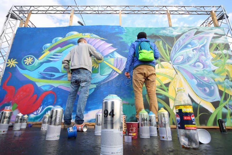 Graffiti des Jungenabgehobenen betrages an den hellen Leuten des Festivals lizenzfreies stockbild