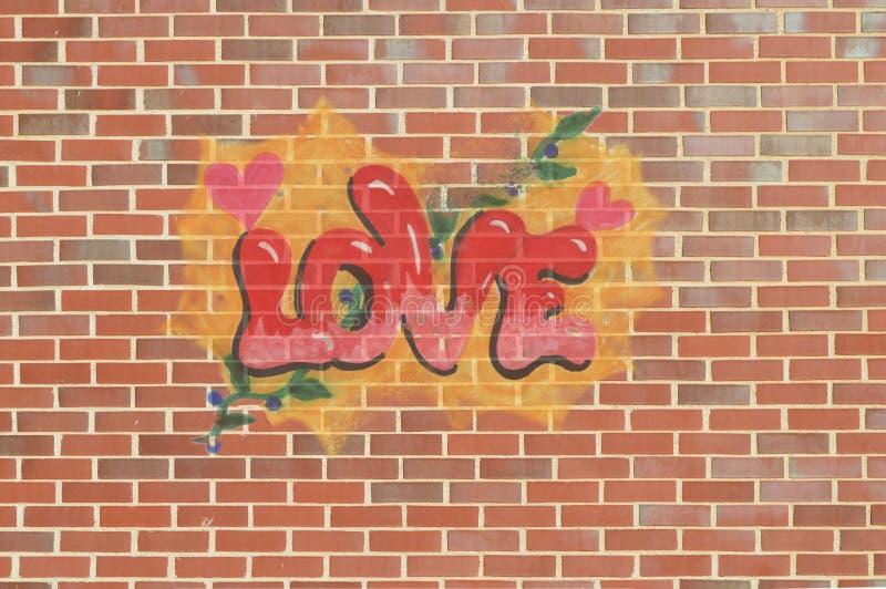 Graffiti des Wortes lieben auf einem Hintergrund einer Wand mit Ziegelsteinen Mit Herzen und Blätter und Beeren lizenzfreies stockfoto