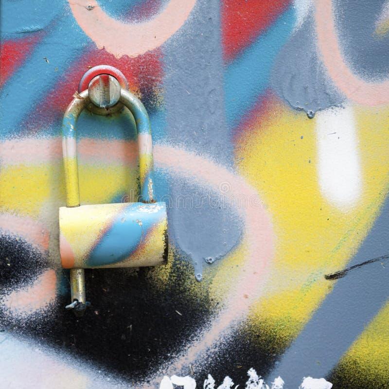 Graffiti geschilderde muur met metaalslot stock foto's