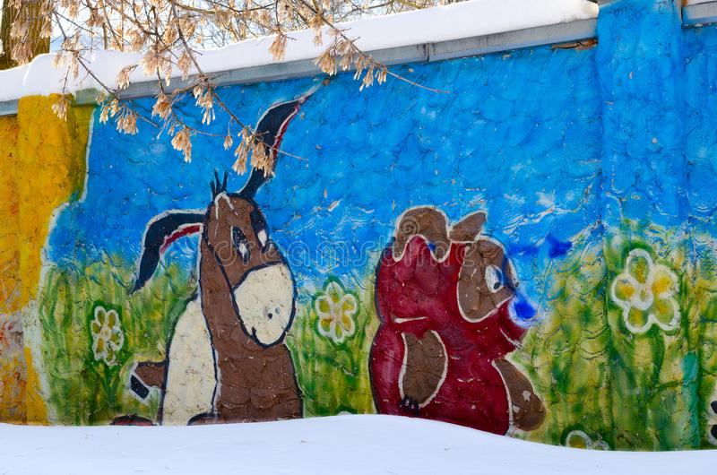 Graffiti with image of cartoon characters bear Winnie Pooh and donkey Ia on concrete fence in city yard, Gomel, Belarus. GOMEL, BELARUS - MARCH 5, 2018: Graffiti royalty free stock images