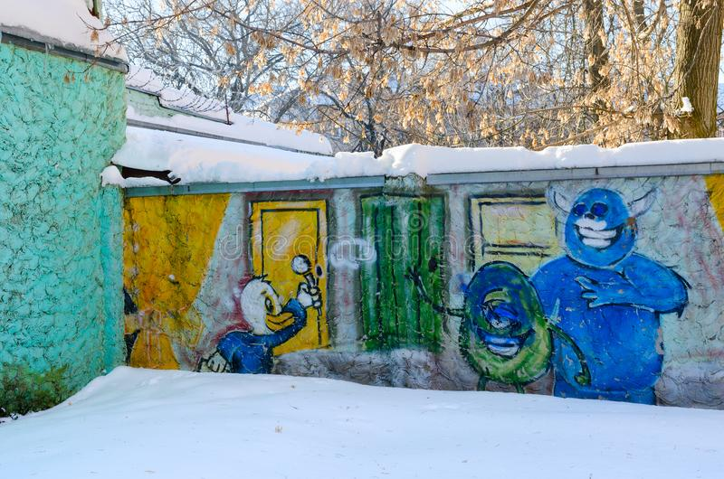 Graffiti with image of cartoon characters on concrete fence in city yard, Gomel, Belarus. GOMEL, BELARUS - MARCH 5, 2018: Graffiti with image of cartoon stock images