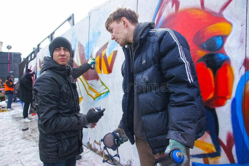 Graffiti jam. MOSCOW - MARCH 17: Spectators look at participants of competition of graffiti at the first stage of city festival «Graffiti jam». on MARCH 17 royalty free stock images