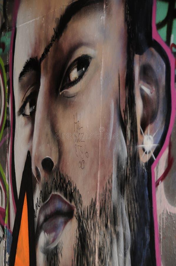 Graffiti depicting a man`s face looking sideways. Graffiti of a man`s face on a wall of the Southbank undercroft skatepark stock images