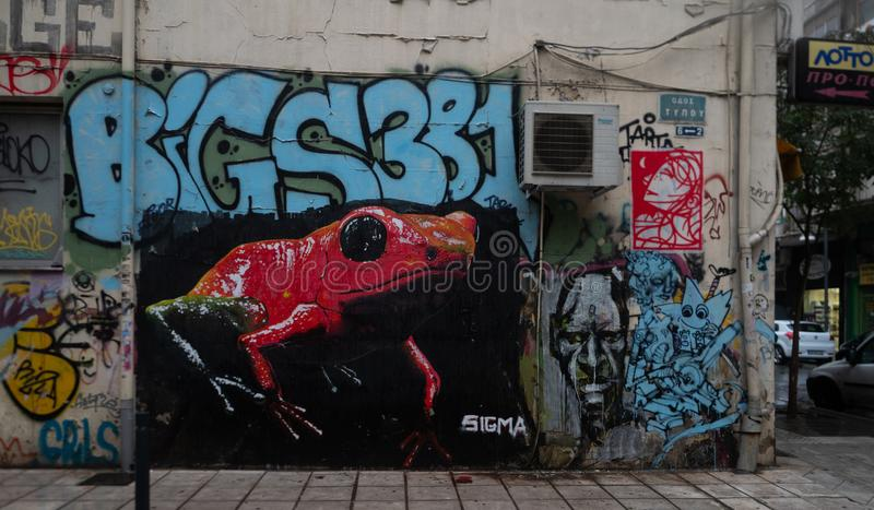 Graffiti mural with writing and dramatic red and green frog in Thessaloniki royalty free stock image