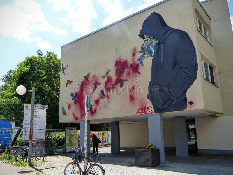 Graffiti of a popular house in Berlin with a boy of whose hood goes out a flock of hummingbird, Germany. royalty free stock photos