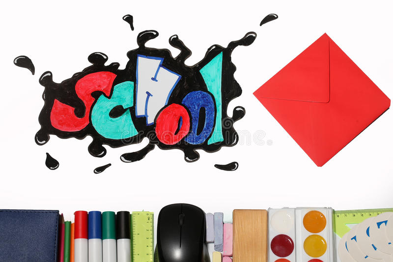 Graffiti school word and supplies. Red envelope and school text word painted graffiti with smiley eyes on paper near pencils markers computer mouse chalk ruler stock image