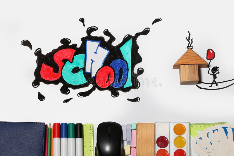Graffiti school word and supplies. School text word painted graffiti with smiley eyes on paper near pencils markers computer mouse chalk ruler paint palette stock photo