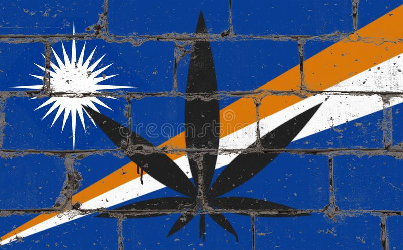 Graffiti street art spray drawing on stencil. Cannabis leaf on brick wall with flag Marshall Islands stock images