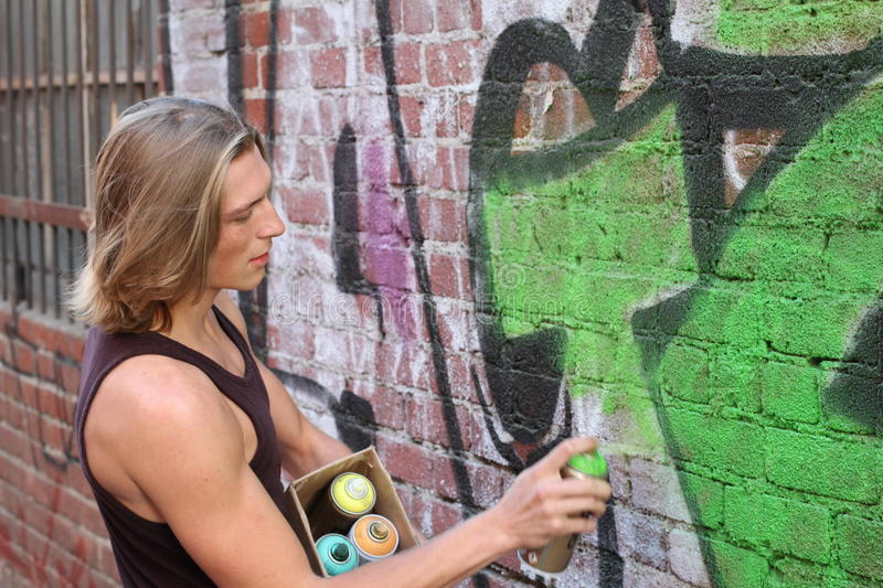 Graffiti street artist with several colors ready to work on his art royalty free stock image