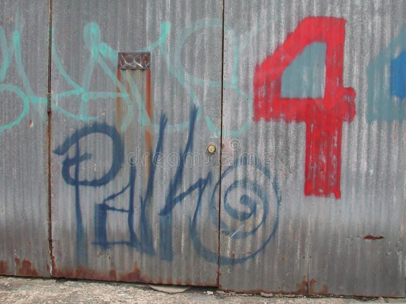 Graffiti su una parete del metallo con 4 verniciati immagine stock libera da diritti