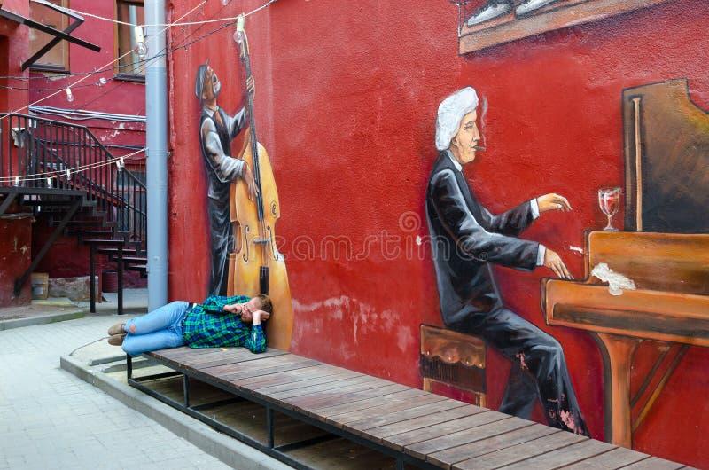 Graffiti sur le mur du pianiste de maison, violoncellist, yard rouge, Minsk, Belarus images libres de droits