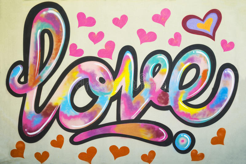 Graffiti text Love on the wall with many pink colored heart shapes around royalty free stock photography