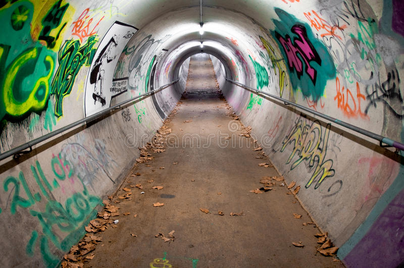 Graffiti Tunnel. Pedestrian tunnel covered with graffiti and neon lights stock image