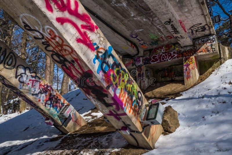 Graffiti under a bridge. In a sunny park in winter stock photography
