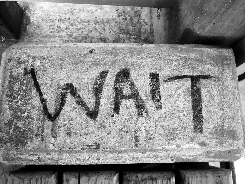 Bench with message to wait stock photography
