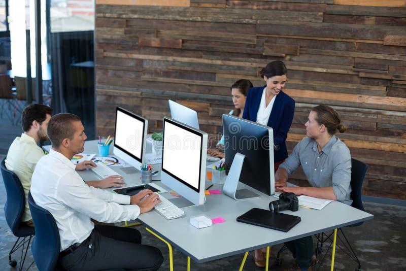 Grafici che interagiscono mentre lavorando al personal computer fotografie stock libere da diritti