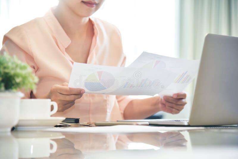 Grafici della tenuta della donna di affari e documento del diagramma di grafico di affari immagini stock libere da diritti