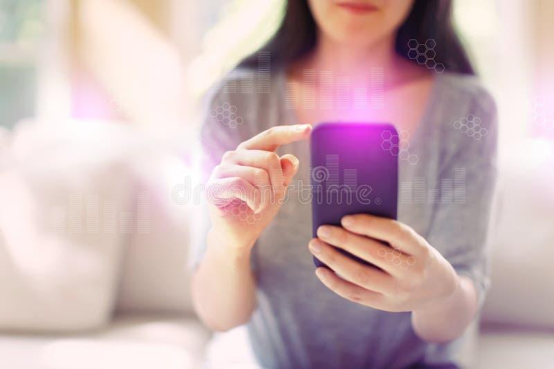 Grafici di Digital e griglie di esagono con la donna che per mezzo di uno smartphone immagini stock