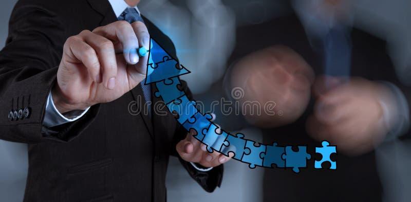 Grafici di puzzle della mano dell'uomo d'affari fotografia stock