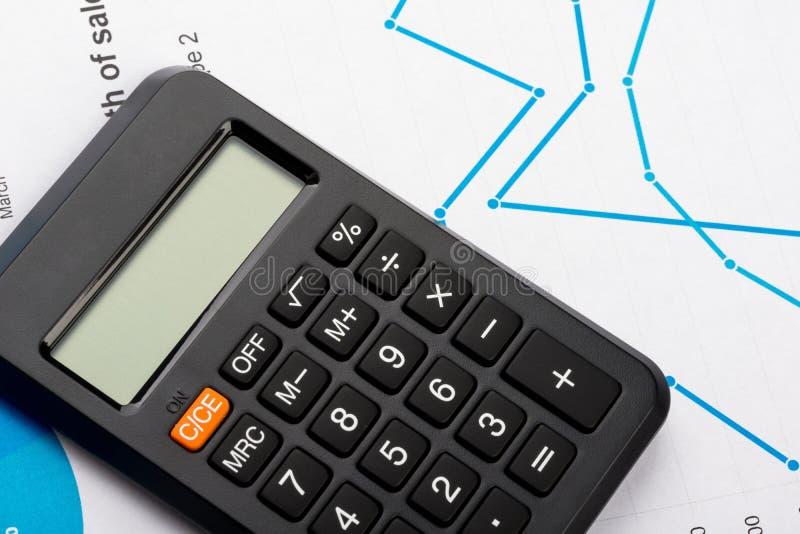 Grafici e analisi tecnica finanziari con il calcolatore fotografia stock libera da diritti