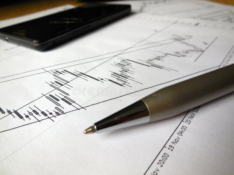 Grafici, penna e telefono cellulare quotidiani immagini stock