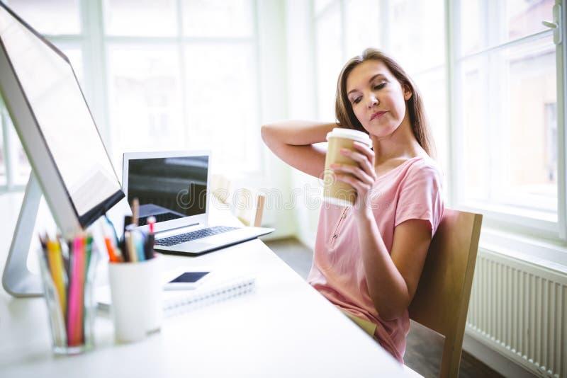 Grafico attraente stanco che tiene la tazza di caffè eliminabile fotografia stock
