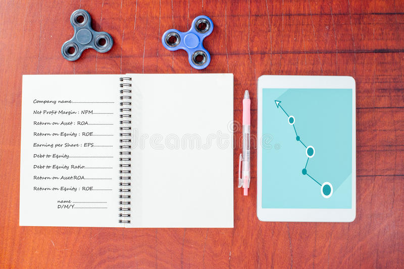 Grafico blu sulla compressa, penna, filatore della mano, taccuino sulla tavola di legno immagini stock libere da diritti