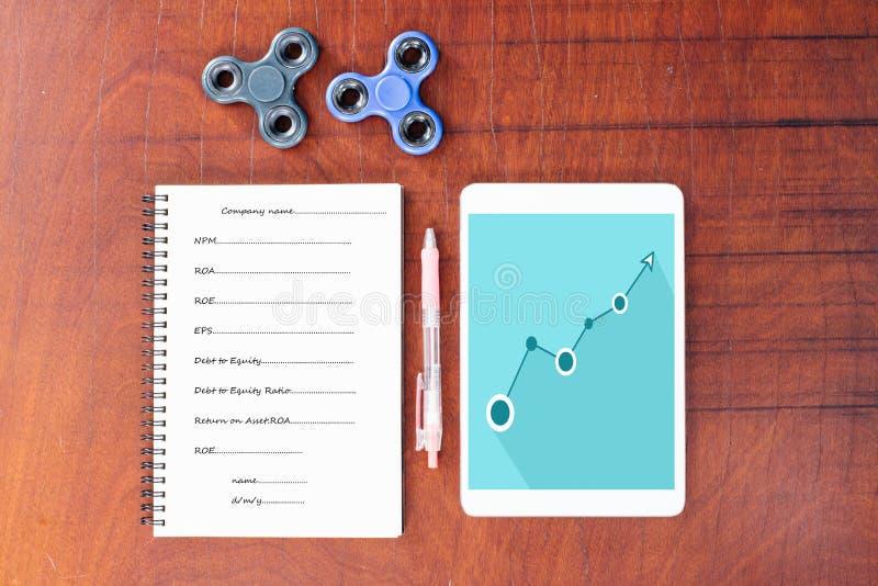 Grafico blu sulla compressa, penna, filatore della mano, taccuino sulla tavola di legno immagini stock